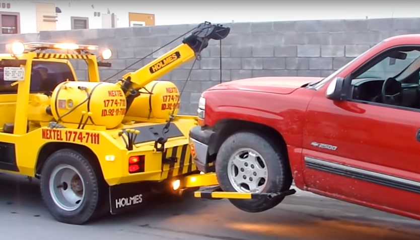 coche rojo llevado por grúa amarilla
