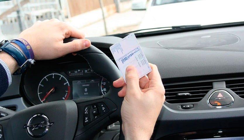 hombre en coche con carnet de conducir
